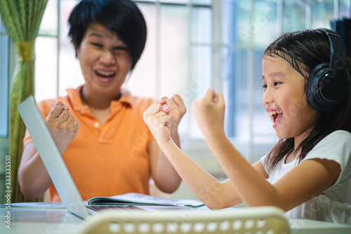 Valokuvatapetti Asian girl and her teacher using laptop for online study during homeschooling at home