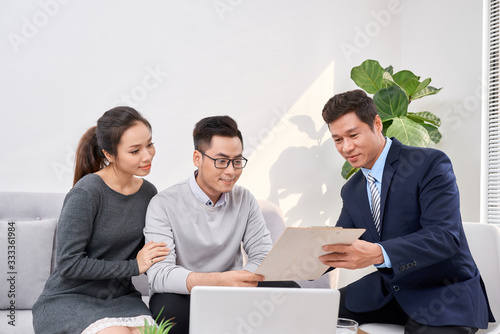 Fototapeta Sales Consultant showing new investment plans to young asian couple obraz