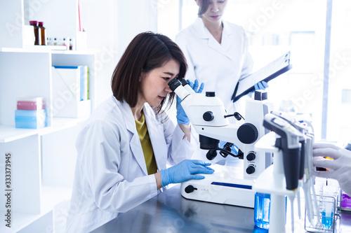 顕微鏡を覗く研究チームの女性 Wallpaper Mural