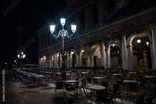 Fotografie, Obraz Empty big street cafe at night, lit by lanterns
