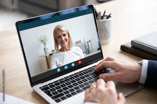 Head shot close up laptop screen view smiling attractive middle aged woman holding video call from home with male business partner, discussing working issues remotely online via videoconference app.