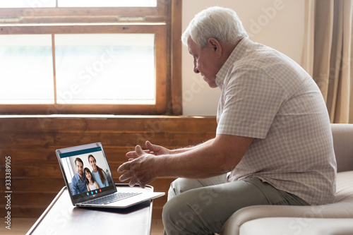Cuadros en Lienzo Happy elderly mature 80s man holding video call with family grown up children and granddaughter, communicating online via laptop videoconference application, staying at home isolation, virus outbreak