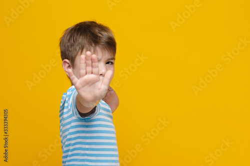 Fototapeta Little cute boy in striped clothes holds out his hand forward in a barrage gesture isolated on a yellow background. obraz
