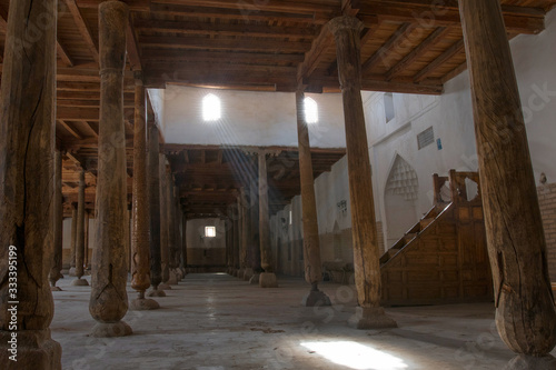 Main hall of Juma mosque (10th and 18th centuries) with old wooden pillars and sunbeams from the window. Khiva, Uzbekistan, Central Asia