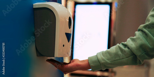 Fotomural Macro shot of young woman using automatic hand sanitizer dispenser at the international airport with blank glowing advertisement banner on background