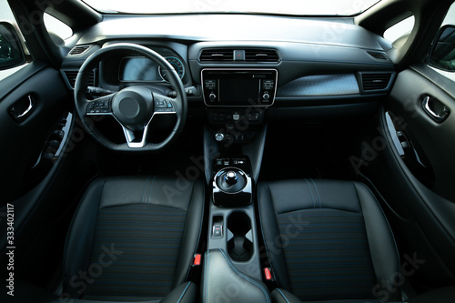 Obraz Electric car interior details of door handle with windows controls and adjustments. Inside car interior with front seats, driver and passenger, textile, windows, door panels, console - fototapety do salonu