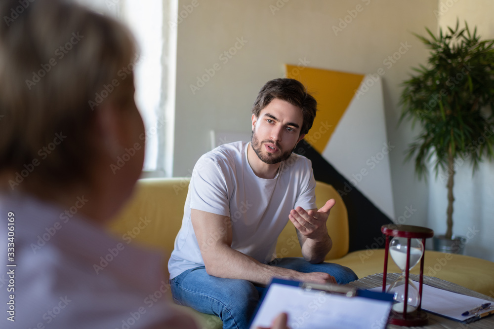 Fototapeta Concerned man sharing thoughts with psychologist