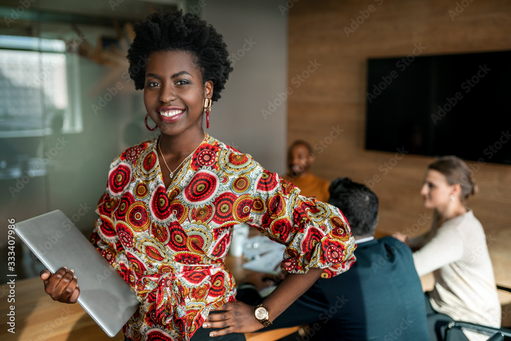 Fototapeta Beautiful young smiling professional black african business woman holding laptop, coworkers hold a meeting in background