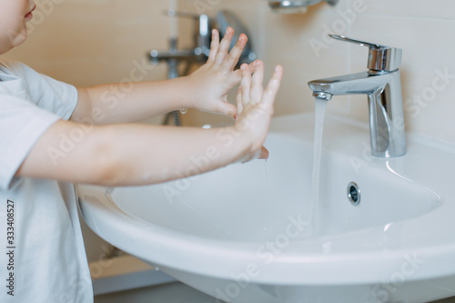 Fototapety, obrazy: How to wash your hands while pandemic of coronavirus. A kid is washing hands with anti-infective soap. Baby girl washing hands and holding white soap.