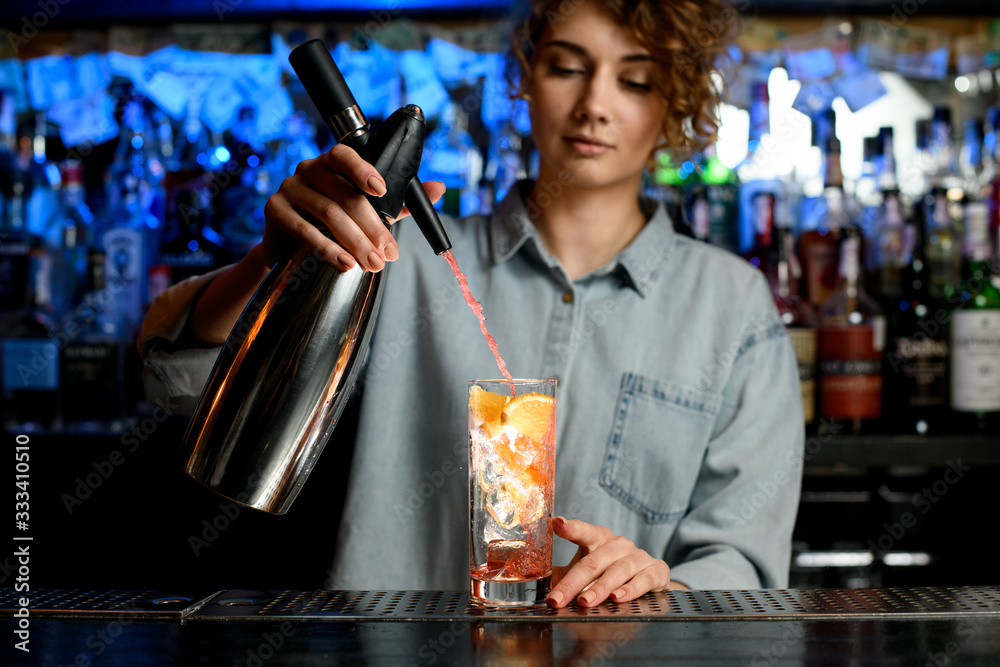 Fototapeta young bartender woman energetically pouring cocktail using steel siphon