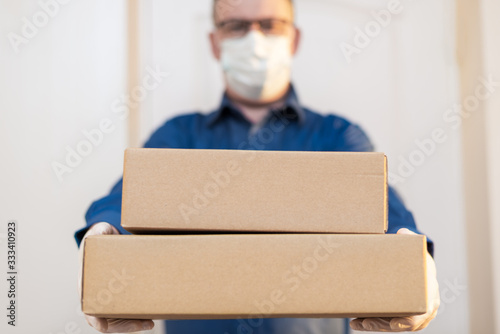Fototapeta courier man delivers the package to the door, contactless delivery obraz
