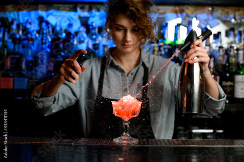Fototapeta woman bartender expressive pouring cocktail from steel siphon to glass on bar counter. obraz