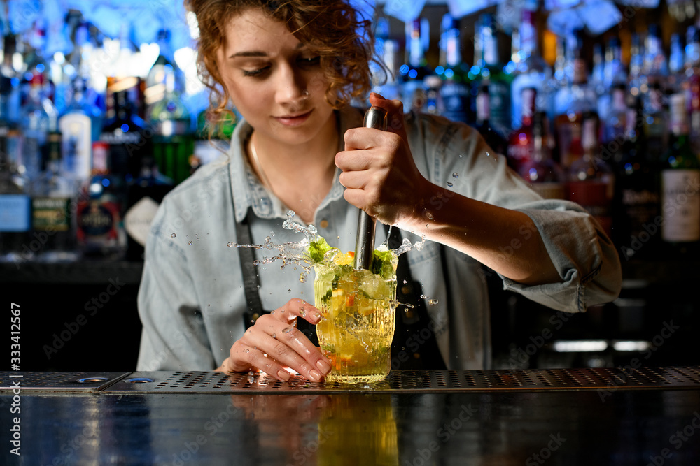 Fototapeta Young woman barman carefully preparing cocktail with slices of citrus fruits