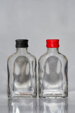 Two Empty  Russian Vodka Glass Bottles With Black And Red Caps On A Grey Background Vertical Image