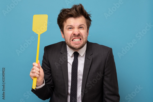 man in suit holding a fly swatter wanting to kill annoying mosquito Wallpaper Mural