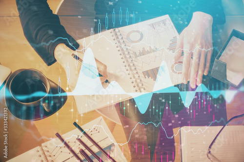 Multi exposure of hands making notes with forex chart huds. Stock market concept.