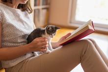 Woman Reading Book And Cuddlin...