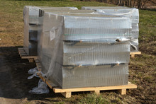 Stack Of Concrete Paving Blocks And Kerbs On A Wooden Pallet. Gray Concrete Slabs For Paving A Road, Driveway Or Patio
