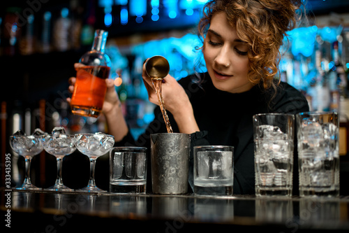Photo Young pretty woman at bar accurate pours brown alcoholic drink into metal glass