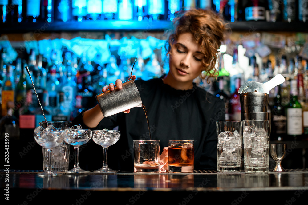 Fototapeta Young woman barman preparing cocktail and pouring it into glass.