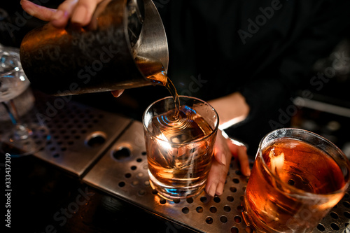 Fototapeta Close-up bartender masterfully pours negroni cocktail into glass on bar counter. obraz