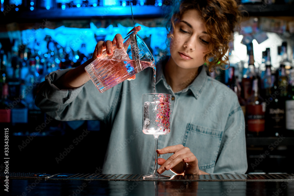 Fototapeta Lady bartender pours pink cocktail into wineglass