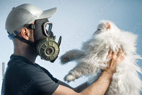A man in a gas mask holds a cat. The man is allergic to pets. Wallpaper Mural