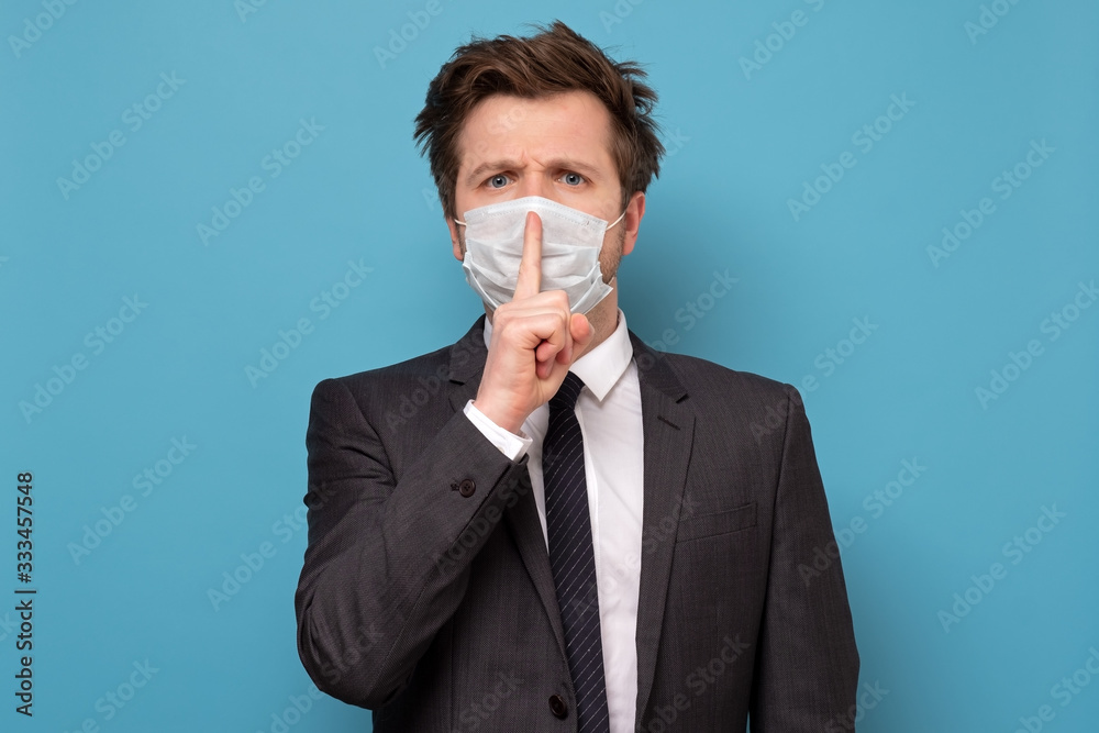 Fototapeta man in medical mask with shh gesture, asking for silence or to be quiet