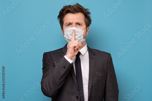 Fototapeta man in medical mask with shh gesture, asking for silence or to be quiet obraz