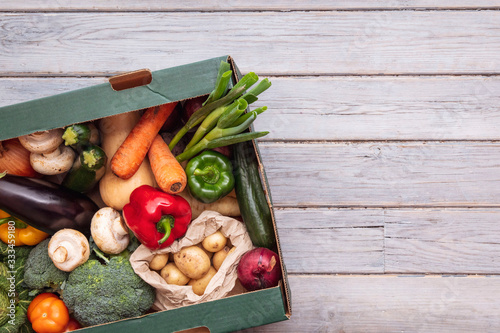Fototapeta Fresh organic vegetable delivery box on a wooden background obraz