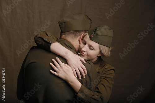 Fotografía Young couple in love in world war Second military uniform hugs as if saying good