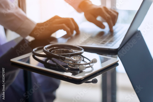 Fotografiet Male doctor hands typing on laptop computer keyboard, search medical information with digital tablet pc and medical stethoscope on the desk at office