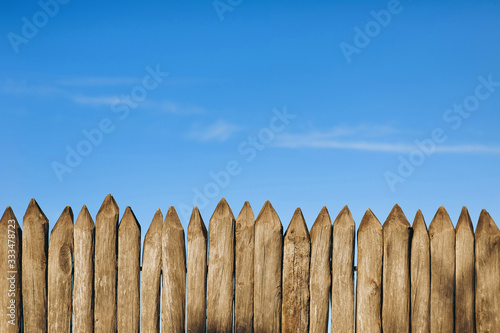 Fence from a stockade fence against the blue sky Tapéta, Fotótapéta