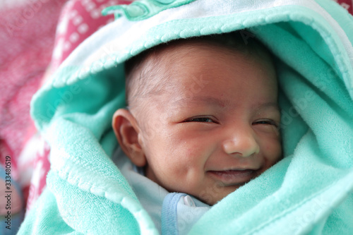 Valokuva a smiling newborn baby with dimple in cheek wrapped in sea green colored towel w