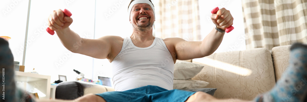 Fototapeta Funny smiling man sitting on fit ball working out