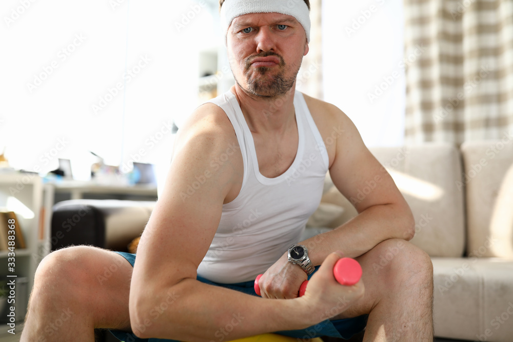 Fototapeta Funny grimacing man sitting on fit ball working out with small pink dumbbells at home