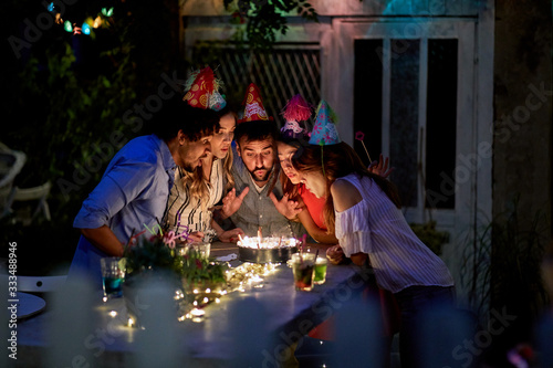 Fototapeta Friends with birtday girl blowing candles on cake obraz