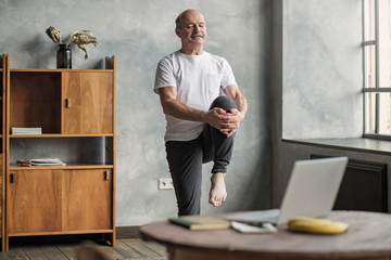 man doing yoga exercise at home using online lesson on notebook.