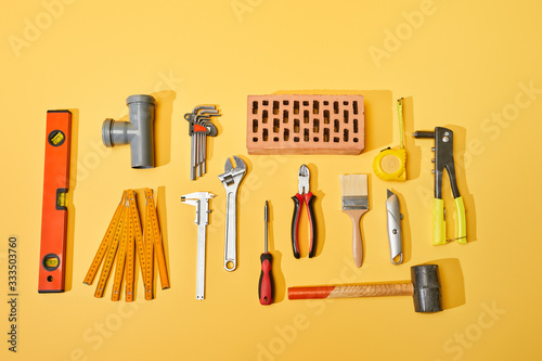 top view of industrial tools and brick on yellow background