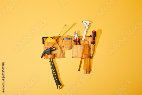 top view of tool belt with hammer, pliers, measuring tape, calipers, screwdriver and folding ruler on yellow background