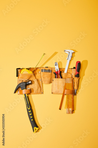 top view of tool belt with hammer, measuring tape, pliers, calipers, screwdriver and folding ruler on yellow background