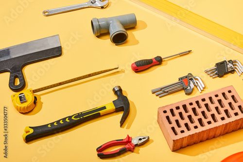 flat lay with hammer, pipe connector, angle keys, screwdriver, pliers, brick, measuring tape and putty knife on yellow background
