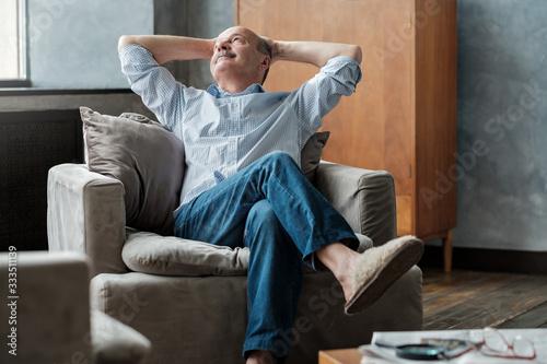 Foto Senior man relaxing in sofa at home sitting alone.