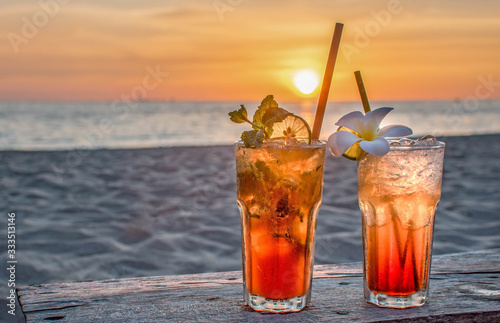 drinks with blur beach and sunset in background Poster Mural XXL