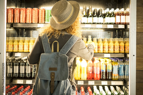 Obraz Travel woman viewed from back choosinf beverage in a fresh fridge - airport or station bar concept and traveler passenger choosing drinks - modern lifestyle backpack people buying drinks bottles - fototapety do salonu