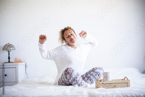 Obraz Early morning wake up concept with happy cheerful caucasian beautiful adult woman stretching and smiling - white colors and light in the bedroom athome or hotel - stay home quarantine - fototapety do salonu