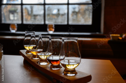 Flight of Scottish whisky, tasting glasses with variety of single malts or blended whiskey spirits on distillery tour in Scotland
