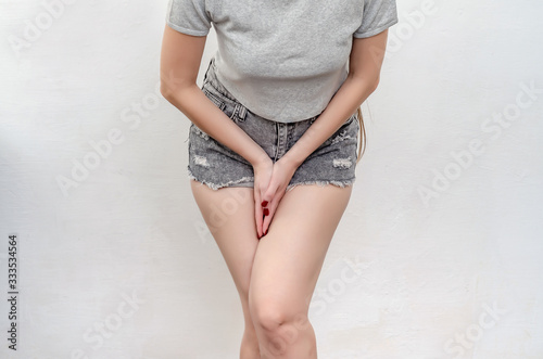 Fotografía Young woman in a jeans shorts standing with her hands between legs