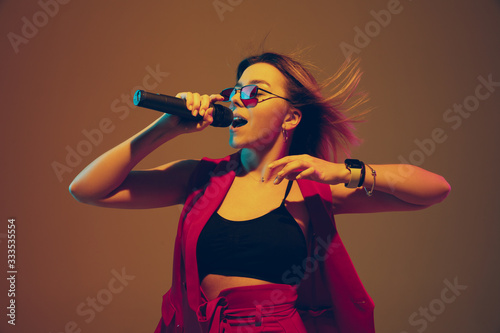 Young caucasian musician, performer singing on gradient background in neon light Fototapet