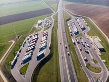 Top View Of The Parking Of Trucks, Gas Station And The Route On Which Cars Rush.
